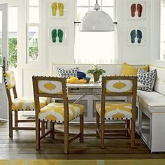 Banquette seating - this L shaped banquette allows for lots of seating and storage.  The crisp white with yellow piping banquette is cheerfully accented with cozy pillows and yellow Ikat patterned fabric on the side chairs.