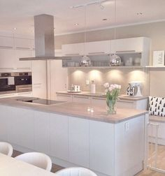 A modern white kitchen creates a more open and light atmosphere. Make your own like this with RAUVISIO crystal glass cabinets. No aluminum frame needed. https://www.rehau.com/us-en/furniture/surfaces/rauvisio-crystal