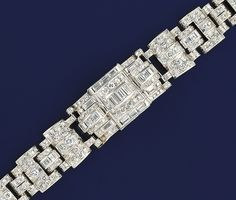 An Art deco diamond bracelet   The central baguette diamond and diamond rectangular geometric panel with matching shoulders to a diamond graduated articulated link braclelet, circa 1930, the centre section reverse formerly fitted with a timepiec