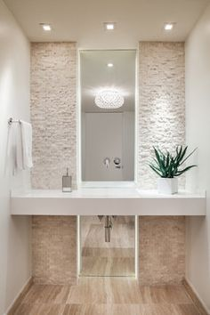 A contemporary cloakroom. Varieties of textures created using the split face tiles in an oyster colour and wooden floors against a very clean and crisp surround.
