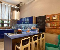 Estúdio do chef com a bancada da cozinha em azul e parede preta para escrever com giz