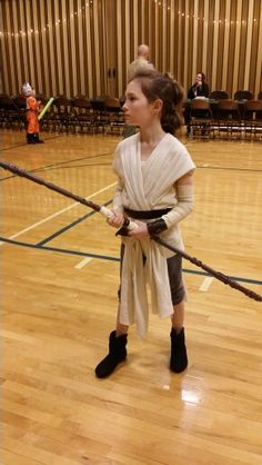 Homemade Rey costume. Cream colored ace bandages for arm sleeves, thrift store shirt cut to style, and gauze fabric strips stained with tea for top, thrift store knit pants cut & gathered at bottom to make shorts, added a toggle to thrift store black boots, belt and arm cuff cut from faux leather upholstry scraps, the pouch that we made from an old medic bag was detachable so she chose to not wear it, the staff was wrapped in gauze at the hand grip areas and a old military style belt cut and…