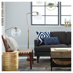 Blues, natural textures and metallics make this living room the perfect take on summer's global trend. Modern pieces like lighting dress up the space, while mixed materials like wood, seagrass and ceramic make it feel homey.