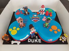 Paw Patrol theme cake with all the PP Pups - Police pup Chase,  Cute, smart Cockapoo puppy Skye, Firedog Marshal, Construction Bulldog Rubble, water-loving Labrador Rescue pup Zuma & Mixed Breed recycling Rocky Plus PAW Patrol's leader Ryder  Red Velvet cake, Cream cheese frosting  in the shape of a bone. Covered & Decorated in coloured fondant. Paw prints, bones & the Paw Patrol team made in fondant toppers.  Happy 1st Birthday Duke