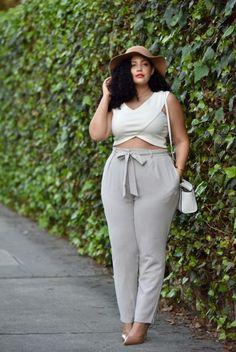 Chica curvi usando un crop top en color marfil con un pantalón gris