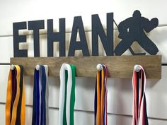 Makes a unique gift for the hockey goalie in your life! This personalized hockey medal display will be the perfect way for them to display all of their well-deserved awards. This design comes in a variety of colors, or you can pick from our other choices of sports or phrases so we can customize it just the way you want!