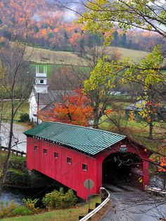 Gorgeous covered bridge with beautiful fall foilage in the background.