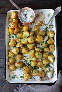 PIECZONE ZIEMNIAKI Z CZOSNKIEM I SOSEM KOPERKOWYM    Fot. Cookmagazine    Składniki:        500 g drobnych młodych ziemniaków      3-4 ząbki czosnku      chlust oliwy z oliwek      sól morska, świeżo mielony pieprz      pęczek koperku      200 g gęstego jogurtu      kilka kropel soku z cytryny      szczypiorek, natka pietruszki    Przygotowanie:    Ziemniaki dokładnie myjemy i kroimy na połówki. W dużym garnku nastawiamy wodę. Solimy, doprowadzamy do wrzenia i wrzucamy ziemniaki.  Piekarnik…