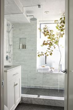 "1""-square tiles on the main floor and in the shower, with white marble (Carrera?) shower threshold, walls."