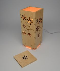 Wooden lamp that measures laser cut and etched with a floral pattern. Lamp is made of Maple wood and finished with a satin polyurethane. Maple top is also included with a laser cut and etched flower.