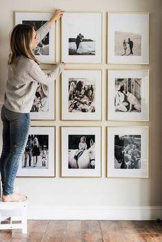 deco mur, blonde fille, manucure noire, cadre doré, parquet stratifié, murs blancs, décoration de salon