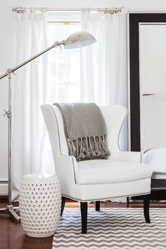 Adore Magazine - bedrooms - bedroom reading corner, reading corner, white curtains, white wingback chair, gray throw, gray throw blanket, ch...