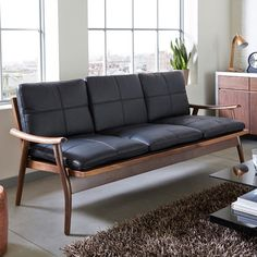 This slightly retro style sofa has a solid walnut frame which supports the loose black leather seat and cushions filled with foam and feather. The cushions have a trendy stitch detail to them. The armrests are designed to suit the curve of the arm. Also available in a two seater.