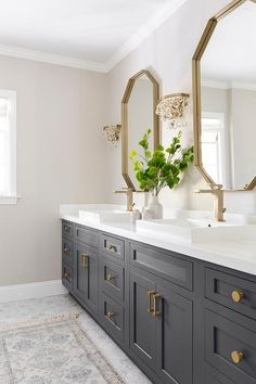 Glass droplets sconces flank a gold mirror over a black bath vanity accented with brass hardware and a brass faucet fixed above an overmount sink. Black Vanity Bathroom, Small Bathroom Paint, Black And Gold Bathroom, Concrete Bathroom, Neutral Bathroom, Brass Bathroom, Bathroom Cabinets, Bathroom Fixtures, Upstairs Bathrooms