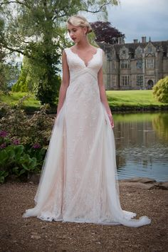 Lois - Relaxed chic. This stylish bias cut lace wedding gown has a V neck that is mirrored front and back. Soft tulle wraps around from the front to become flowing ties on the back. The neckline, hem and train are all edged with a lace scallop.