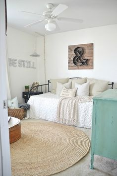 Iron day bed, linen cushions and white walls. How to style a spare bedroom. For more like this, click the picture or see www.redonline.co.uk