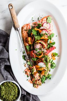 Think peas, mint, pistachios and carrot tops, all blending together to make one vibrant and earthy pesto. That's what is spooned on this roasted salmon and just like that dinner is done!