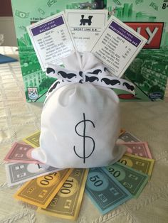 Monopoly centerpiece by my sister-in-law for my brother's 40th birthday party - picture only: half ball styrofoam and stuffing inside bag, mustache-themed ribbon, Monopoly game cards with game piece hot glued to dowel, sitting on fan of Monopoly money