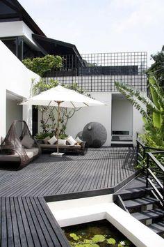 terrasse en bois ou composite, équipement original d'extérieur et un parasol blanc