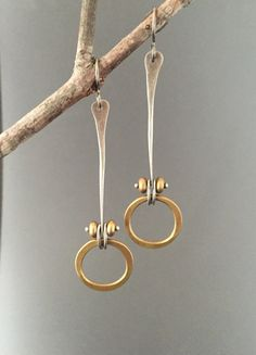 I have forged rings of solid brass to give them a slight organic shape. They are suspended below a forged wishbone of sterling silver, held in place with a small sterling heat river and brass beads. They are simple and elegant. Earrings measure approximately 2 5/8 inches long from the top of the earwire to the bottom of the brass ring. Hypo-allergenic titanium earwires. Brushed patina finish. Each pair will vary slightly from those shown here. Smaller version also available in my shop…