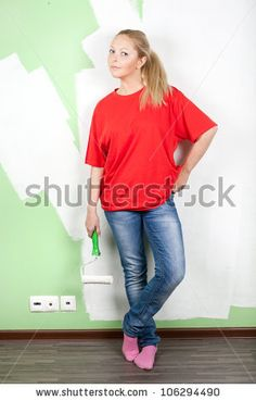 Woman with paint roller in hand standing near painting wall - stock photo