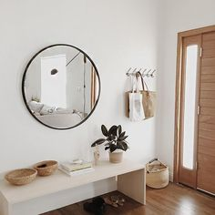 Stunning mimal entryway. I'm in love with an oversized round mirror and a simple bench.
