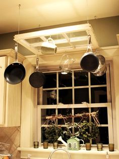 DIY Pot Rack Ideas: A recycled window finds new purpose as a hanging pot rack while still allowing the light to shine through.