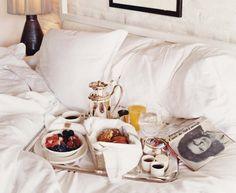 Desayuno en la cama, sábanas blancas.