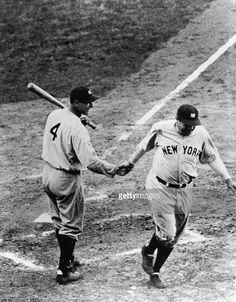 First baseman Lou Gehrig #4 of the New York Yankees shakes hands with teammate Babe Ruth #3 as he crosses the plate during a 1932 World Series game against the Chicago Cubs. The Yankees won the Series.