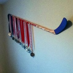 Medal display for hockey. Could also do a similar thing with a baseball bat to hang all his ball caps. Both sports represented.