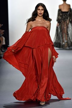 This elegant and sexy  red satin strapless gown with side baring slits Michael Costello RTW Spring 2017 collection.