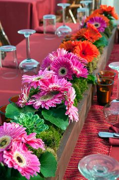 In the center of each table, a long wooden trough contains moss, orange and pink gerbera daisies and green succulents.