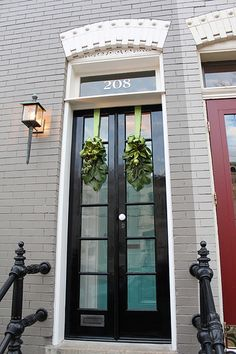 a beautifully simplistic classic back entry with narrow french door & transom and black iron railings