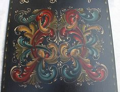Norwegian Rosemaling done in Gudbrandsdal Slye on a Bass Wood Plaque *This Plaque is 18 high, by 12 wide and 3/4 thick, is made out of Bass Wood, and has mirrored scrolls on top and bottom. *The back ground color is Deep Blue BM acrylic paint. *The Rosemaling is done in various