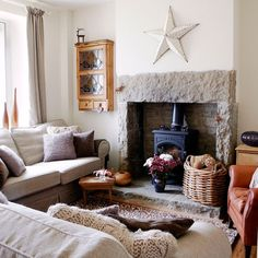Textural country living room Soft, comfy sofas piled high with textural cushions face in towards a stone fireplace to create a snug cocoon of a living room. A mixture of finishes - from stone, to wicker to wool and leather - blend beautifully to form this country-chic space.