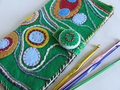 tutorial for a crochet hook booklet/case, but what I really love is the design using felt circles, yarn, and embroidery!