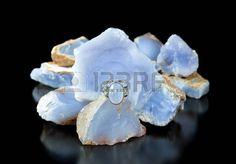 Un oro y un anillo azul calcedonia turco de plata con piedras en bruto en el fondo photo