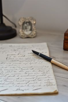 Feather Pen And Inkwell With Old Handwritten Journal Beneath Image