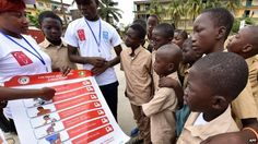 Volunteers wearing United Nations Development Programme (UNDP) T-shirts show a placard to raise awareness about the symptoms of the Ebola virus to students of the Sainte Therese school, in the Koumassi district, in Abidjan, Ivory Coast - 15 September 2014