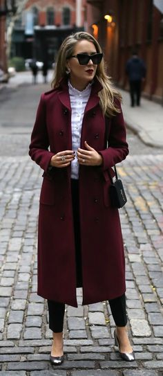 Long burgundy double-breasted coat, metallic silver ankle strap pump, tailored high-waisted black pants, white ruffle blouse, black shoulder bag, deep red lip { Saint Laurent, Valentino, Theory, winter style, what to wear to work, holiday outfits, casual business attire, classic style} #silveranklestrapsheels