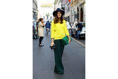 Eleonora Carisi: pull giallo fluo, pantaloni flare e maxi clutch effetto snake