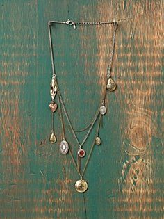 Beautiful layered necklace with mixed metal chains and varied locket charms. Lobster claw closure.