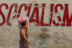 A Cuban woman walks home from the market past a mural painted by the Committee for the Defense of the Revolution along San Lazaro Street in the Vedado district January 26, 2015 in Havana, Cuba. As diplomats work to reestablish diplomatic ties between Cuba and the United States, Cubans face a new reality that could mean less restricted travel between the former Cold War enemies and easier access to telecommunications technology, building materials and American food products.