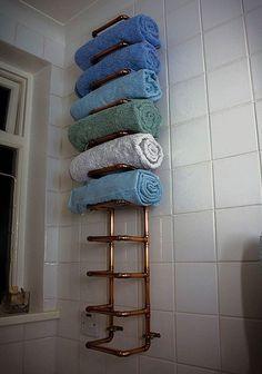 Se o banheiro é pequeno e não tem espaço para um armário, vale organizar as toalhas com divisórias feitas com os canos