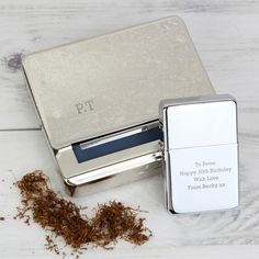 Our personalised Tobacco Tin and Silver Lighter Set are ideal keepsakes for any recipient.   The lighter can be personalised with 4 lines of text, with up to 20 characters per line. The tobacco tin can be personalised with 3 characters.   Please note that all text is case sensitive and will appear as entered.   The lighter does not come supplied with fluid.   Oil Lighter.   The tobacco tin is made from steel and can be used to roll and store cigarettes.  Please note we cannot ship this item…