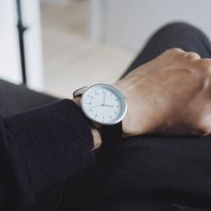 Super clean and minimalist mens watch. Has a very minimalist white watch  face with black hour and minute hands and a yellow second hand.      * 40mm diameter     * 7mm thick     * Black leather strap     * 18mm band width     * Buckle clasp     * Water resistant down to 30 meters