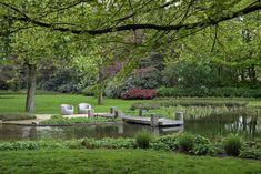 Tuin in landelijke stijl met een gave vijver en steiger gemaakt van oude meerpalen uit de Antwerpse haven.