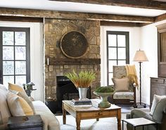 Stone floor-to-ceiling fireplace, paned frame windows, exposed beams, neutral palette
