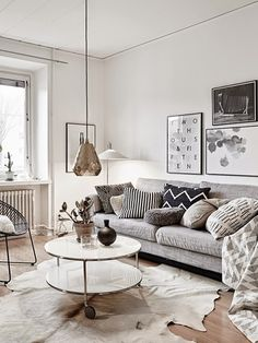 グレーやホワイトの、淡いモノトーンカラーのファブリックがベースのお部屋です。ベージュベースのカウハイドラグを中心に敷いて、床の色との調和を図っています。ちょっと低めの照明や、壁面のアートフレームもポイントです。