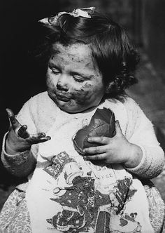 A little girl covered in chocolate as she tackles an Easter egg, 17th March 1938.